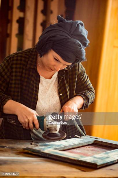 Young Restorer Woman Working with Machine Grinder
