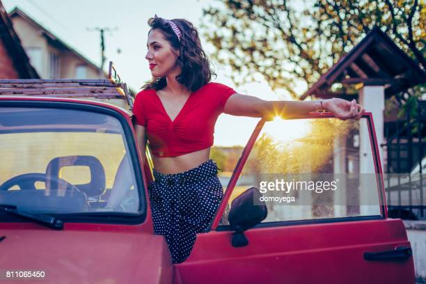 Young retro styled woman in vintage car