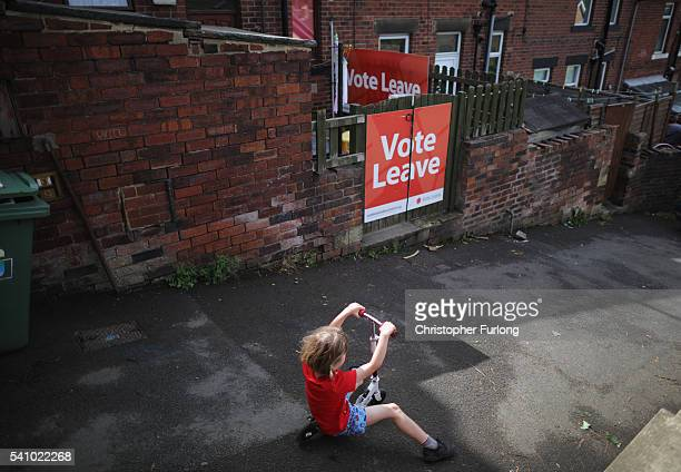 A young rides his scooter past a 'Vote Leave' poster in the back alley next to his home in the West Yorkshire town of Batley in the constituency of...