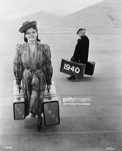 A young Rita Hayworth sees in the New Year with a pair of '1941' suitcases as she passes writer Quentin Crisp carrying a pair of '1940' suitcases on...