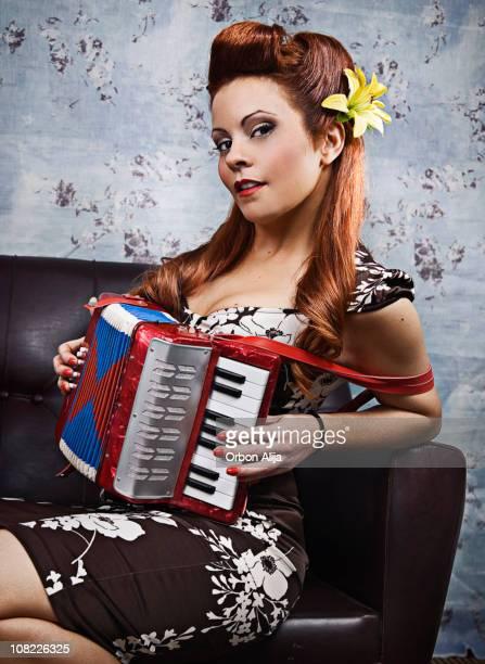 Junge Rockabilly Frau spielt Akkordeon auf Couch