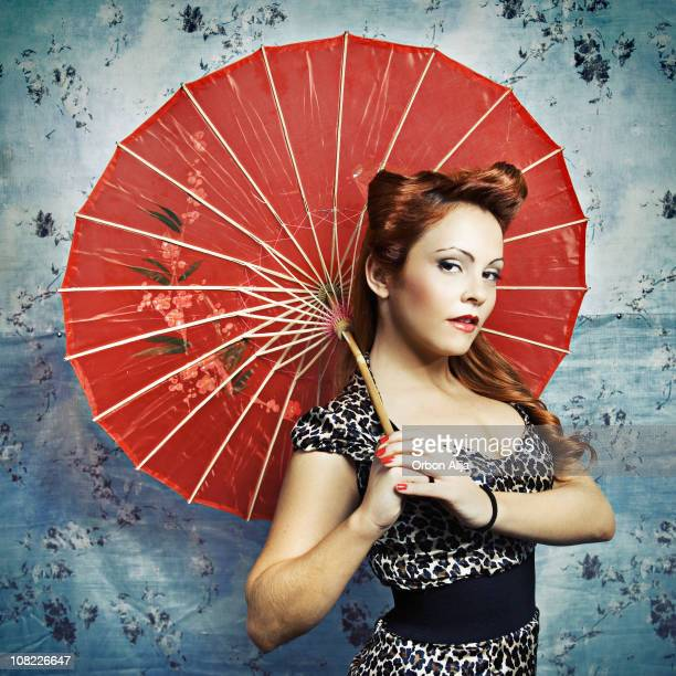 Young Rockabilly Woman Posing with Parasol Against Wall
