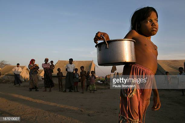 A young Rohingya girl carries water to her tent at a IDP camp November 24 2012 on the outskirts of Sittwe Myanmar An estimated 111000 people were...
