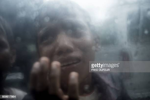TOPSHOT A young Rohingya Muslim refugee begs for food through the glass of a car at Balukhali refugee camp in Bangladesh's Ukhia district on October...