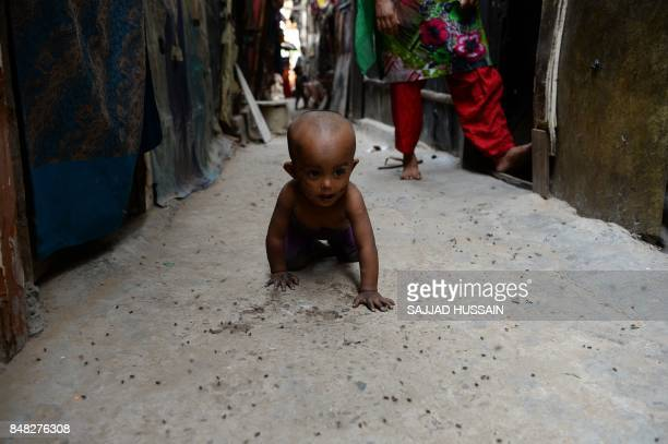 A young Rohingya refugee crawls through an alley way outside a makeshift shelter in New Delhi on September 17 2017 Detested in Myanmar the Muslim...