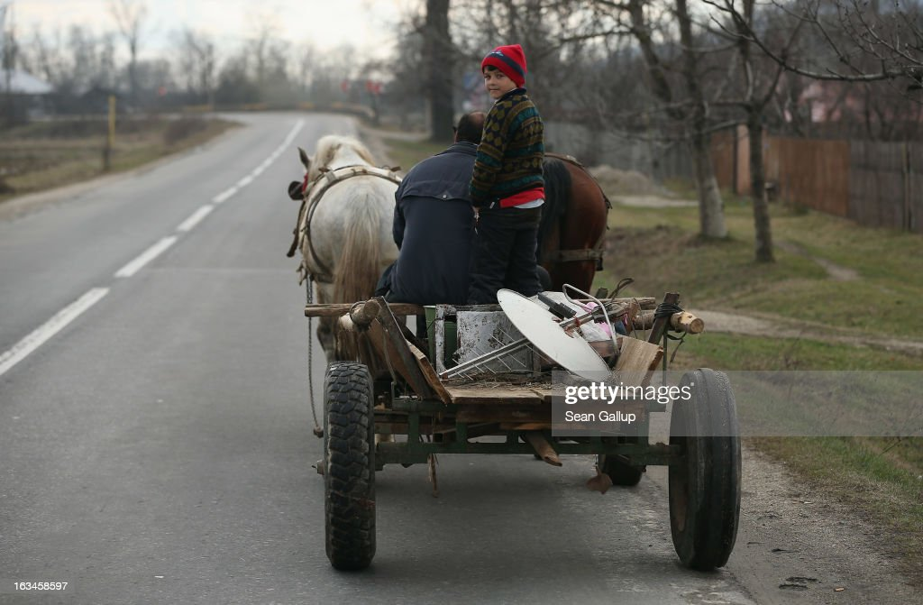 A young Roma boy rides with his father transporting goods on a horse-drawn cart along the main road on March 10, 2013 in Cismea, Romania. Horse-drawn carts are still a common site in Romania, especially among the Roma minority, though the government recently banned horse-drawn carts from major cities. Both Romania and Bulgaria have been members of the European Union since 2007 and restrictions on their citizens' right to work within the EU are scheduled to end by the end of this year. However Germany's interior minister announced recently that he would veto the two countries' entry into the Schengen Agreement, which would not affect labour rights but would prevent passport-free travel.