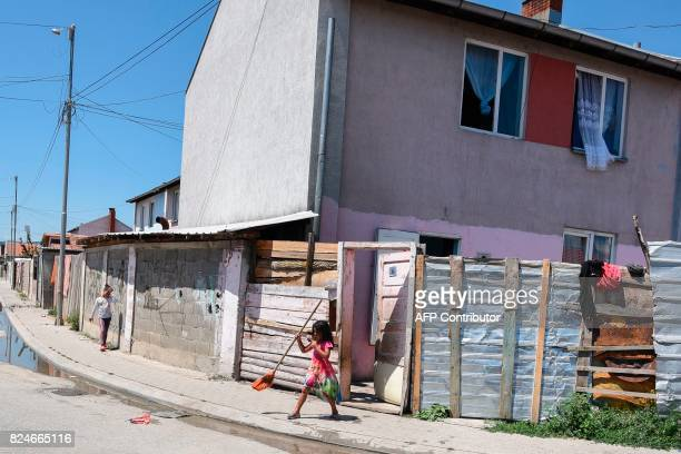 A young Roma child sweeps in front of her house in the Roma neighborhood in the town of Mitrovica on July 7 2017 The Roma 'are not treated like...