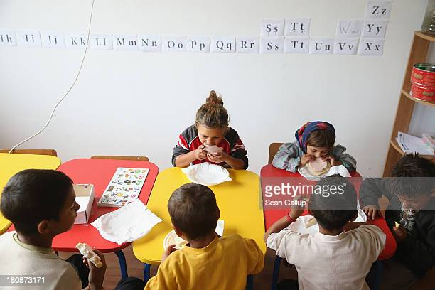 Young Roma children eat bread and ham during snacktime at a preschool class in the abjectly poor Roma settlement of Ponorata on September 10 2013 in...
