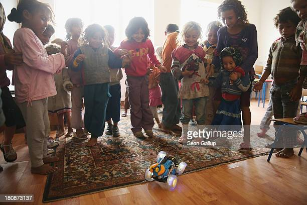 Young Roma children take delight in a remotecontrolled illuminated toy car during a preschool class in the abjectly poor Roma settlement of Ponorata...