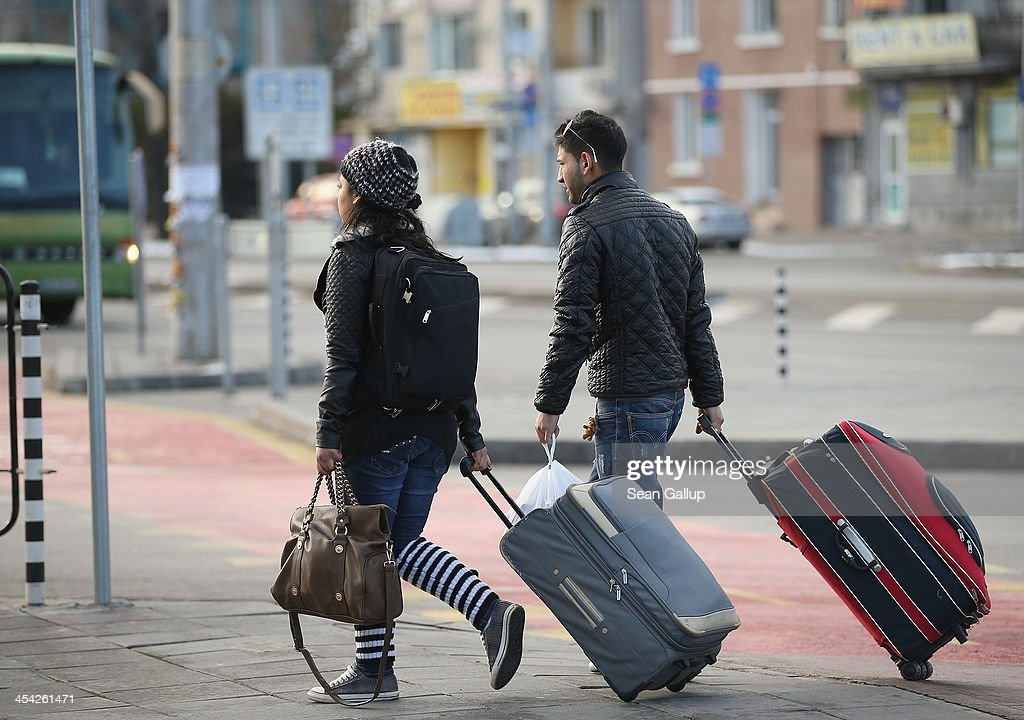 A young Roma couple walk with suitcases outside the main bus station on December 7, 2013 in Sofia, Bulgaria. Restrictions on the freedom of Bulgarians and Romanians to work in the European Union are due to run out by December 31, though several EU leaders, including British Prime Minister David Cameron, are considering imposing temporary restrictions to cut the flow of Romanians and Bulgarians arriving in EU countries. Many EU nations have voiced concern over too many Bulgarians and Romanians arriving and applying for social benefits. Romania and Bulgaria are both EU members though their citizens do not yet receive the same rights as citizens of other EU nations.