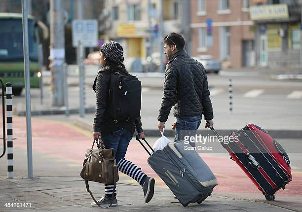 A young Roma couple walk with suitcases outside the main bus station on December 7 2013 in Sofia Bulgaria Restrictions on the freedom of Bulgarians...