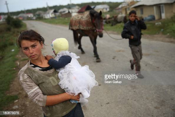 Young Roma mother Claudia Varga holds her infant daughter Raluca on the only street in the abjectly poor Roma settlement of Ponorata on September 11...
