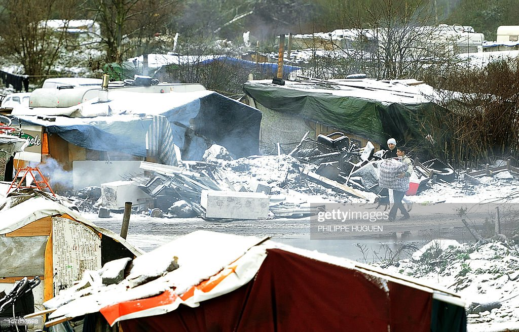 Young Roma people are pictured walking in their camp covered by snow in Lille on December 7, 2012.