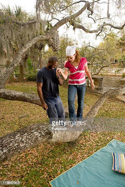 Young romantic couple balancing on oak tree branch