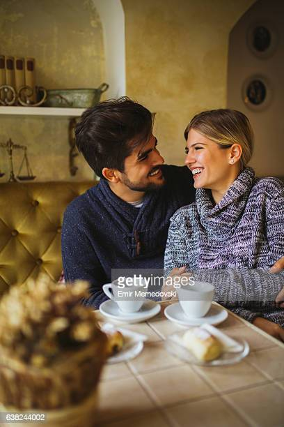 Young romantic couple flirting over coffee and dessert