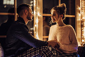 Young romantic couple is spending time together at home in pajamas.Sitting on window sill with garland in New Year Eve.Waiting for Christmas.Two lovers are hugging and kissing in Saint Valentine's Day