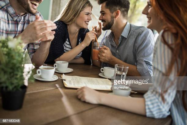 Young romantic couple sharing mocktail while being with friends in a cafe.