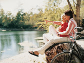 Young Romantic Couple Sitting on a Log at the Edge of a Lake Looking at the View