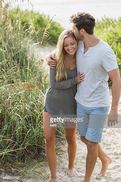 Young romantic couple walking on beach sand dunes