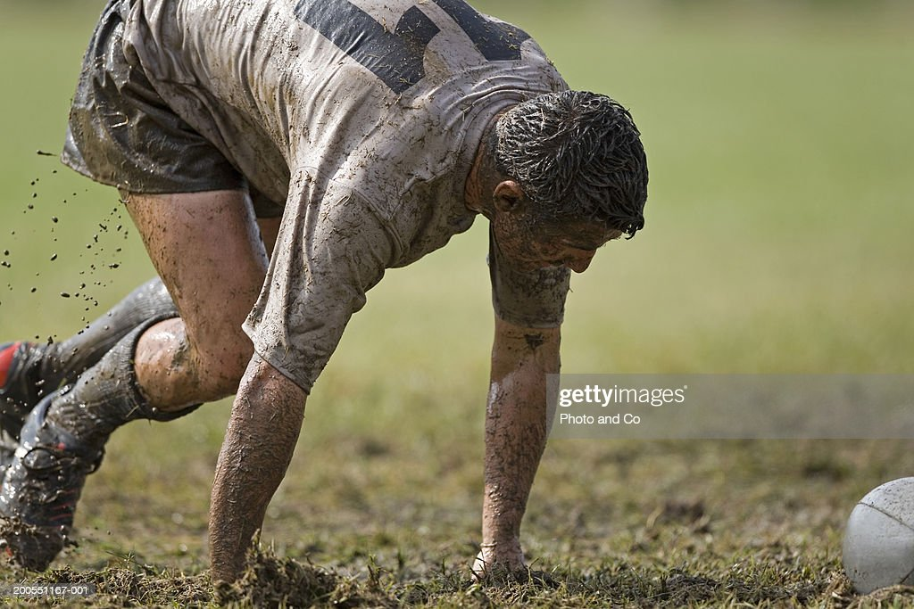 Young rugby player covered in mud, approaching ball : Stock Photo