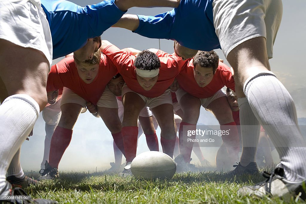 Young rugby players forming scrum in field : Stock Photo