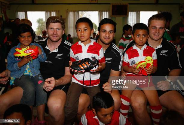 Young rugby players Margaret LeeHang Manuel LeeHang and Brewstar Taupau sit on the knee of All Blacks Adam Thomson Piri Weepu and Sam Cane after...