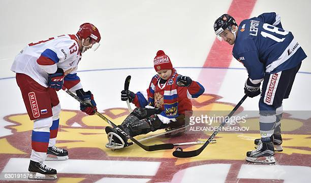 Young Russian sledge hockey player Artyom Denisov throws a puck during a symbolic face off to Russia's forward Pavel Datsyuk and Finland's defenceman...