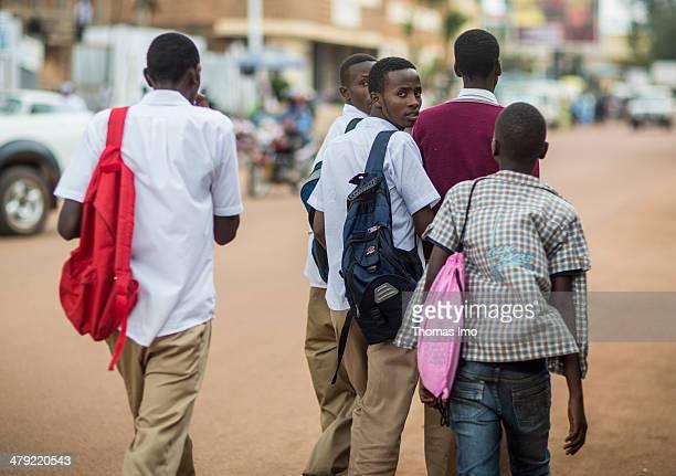 Young Rwandan men walking across a dusty road in a Rwandan city on February 05 2014 in Huye Rwanda