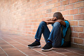 Young boy sitting alone with sad feeling at school. Depressed african child abandoned in a corridor and leaning against brick wall. Bullying, discrimination and racism concept at school with copy spac
