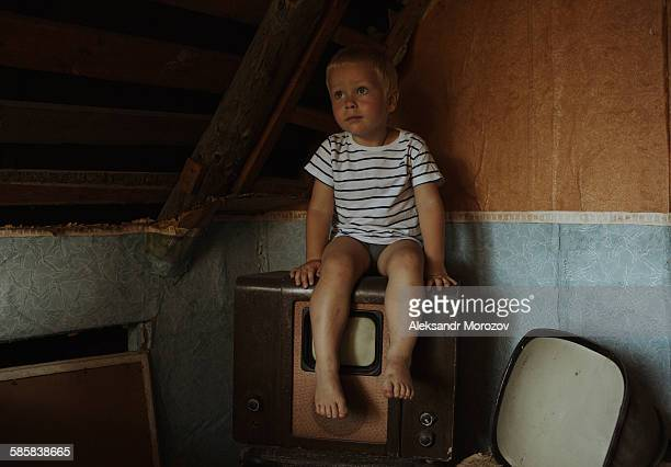 Young sad boy in the attic
