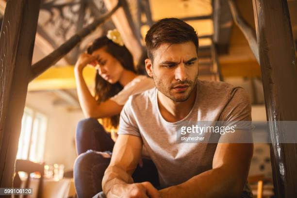 Young sad man having relationship difficulties with his girlfriend.