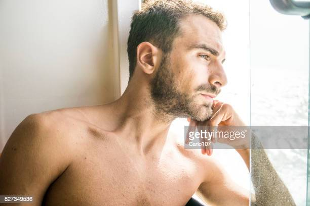 Young sad man looking out of the window on a ferry boat