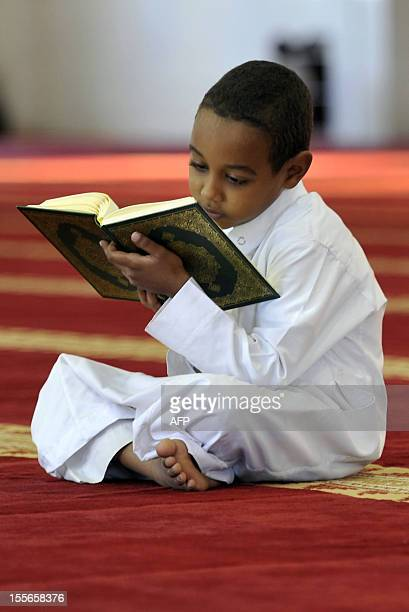 A young Saudi boy reads from the Koran at a mosque in the Red Sea port city of Jeddah on August 27 2010 prior to breaking the daylong Ramadan fast...