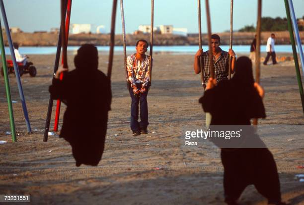 Young Saudi men and women flirt from a distance seated on swings on one of Jeddah's beaches during the festivities of the EidulFitr on December 2002...