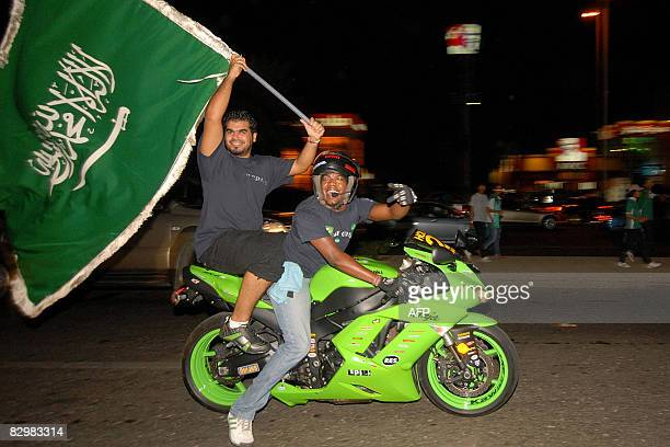 Young Saudis wave the Saudi flag as they celebrate their country's national day late September 23 2008 in the Red Sea port city of Jeddah Saudi...