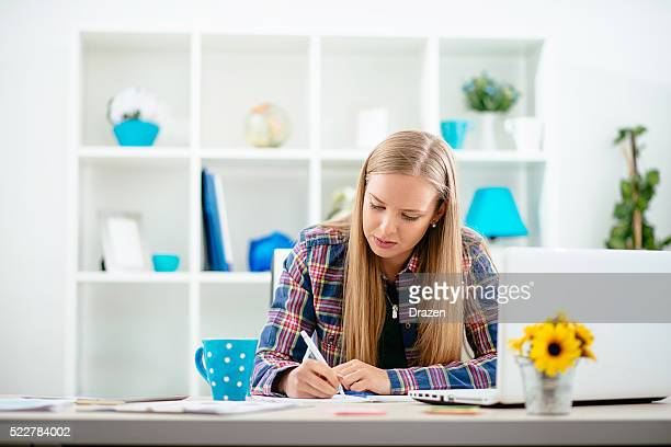 Young Scandinavian businesswoman in start-up office writing project