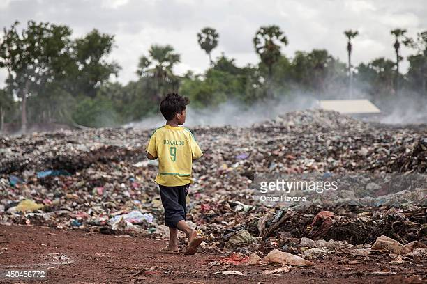 A young scavenger wearing a Brazilian national football team tshirt walks near a burning pile of trash in the Anlong Pi landfill on June 11 2014 in...