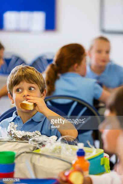 Young School Boy In Uniform Eating A Healthy Lunch
