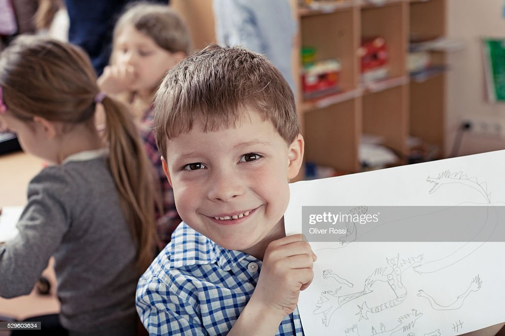 Young school boy (8-9) showing his drawing : Stock Photo