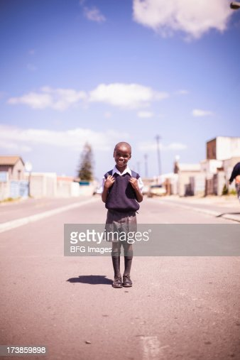 Young school boy standing proudly in street in township
