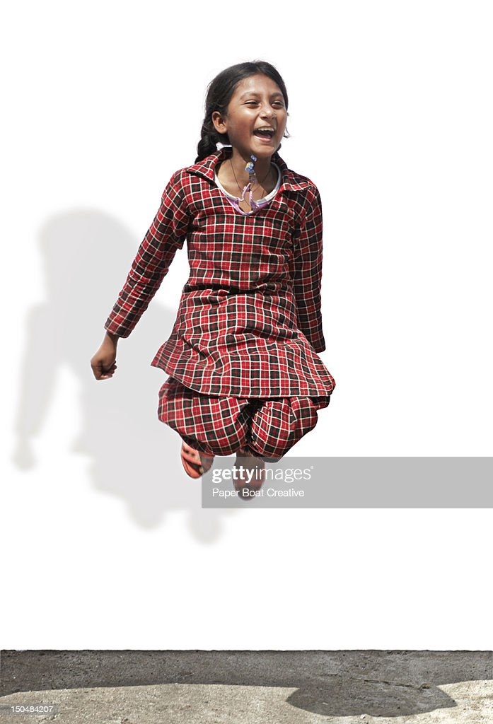 Young school girl jumping up in the air