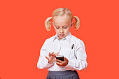 Young school girl reading text messages over orange background