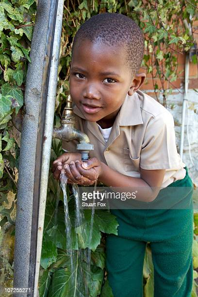 Young schoolboy drinking water from a tap, KwaZulu Natal Province, South Africa
