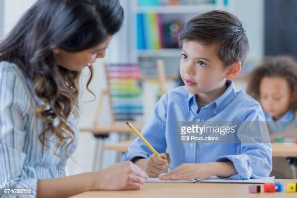 Jonge schooljongen werkt met zijn leraar op school