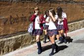 Young schoolchildren students strolling in Calle Sacramento in Leon Castilla y Leon Spain