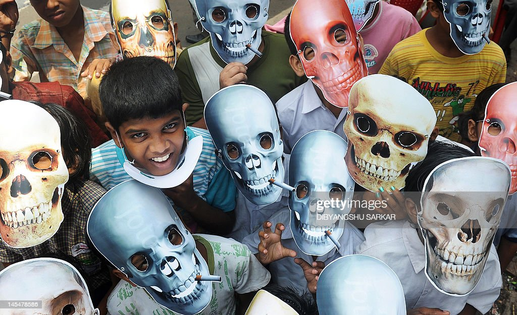 Young schoolchildren wear anti-smoking masks during a 'No Tobacco' rally in Kolkata on May 31, 2012. World No Tobacco Day is observed around the world every year on May 31 and is one of the important World Health Awareness days organized by the World Health Organisation (WHO). AFP PHOTO/Dibyangshu SARKAR