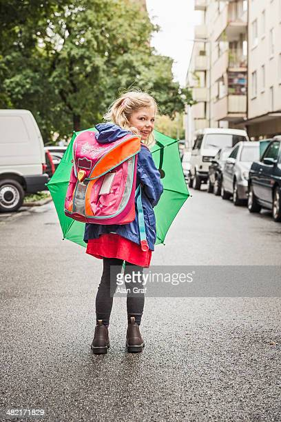 Young schoolgirl carrying umbrella