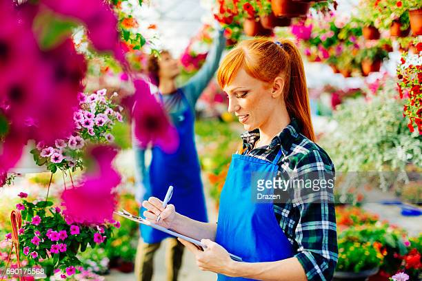 Young science intern examines flowers in plant nursery