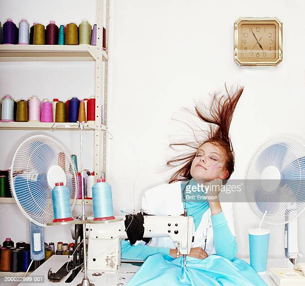 Young seamstress at sewing machine, fan blowing hair