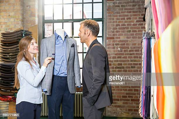 Young seamstress discussing jacket with customer